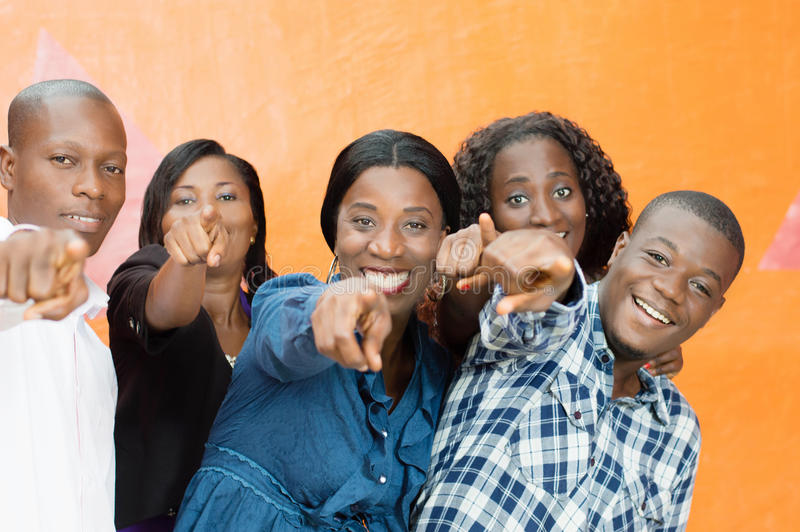 Group of happy friends and designating someone. This group of young friends happy designate someone telling him that it was he they want stock photography