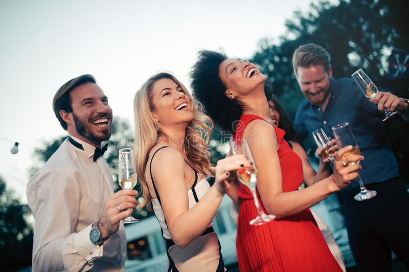 Group of happy friends drinking champagne and celebrating New Year stock images