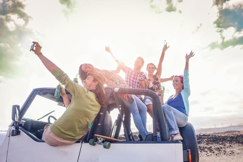 Group of happy friends having fun on convertible car in vacation - Young people drinking champagne and taking selfie stock photography