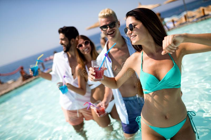 Group of happy friends having fun dancing at swimming pool outdoors. Group of happy friends having fun dancing at swimming pool with cocktails royalty free stock photography