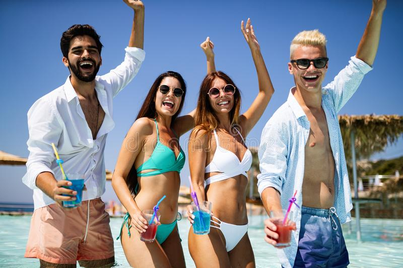 Group of happy friends having fun dancing at swimming pool outdoors. Group of happy friends having fun dancing at swimming pool with cocktails royalty free stock images