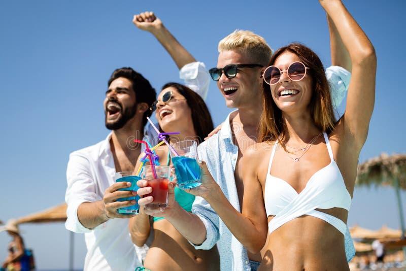 Group of happy friends having fun dancing at swimming pool outdoors. Group of happy friends having fun dancing at swimming pool with cocktails royalty free stock image