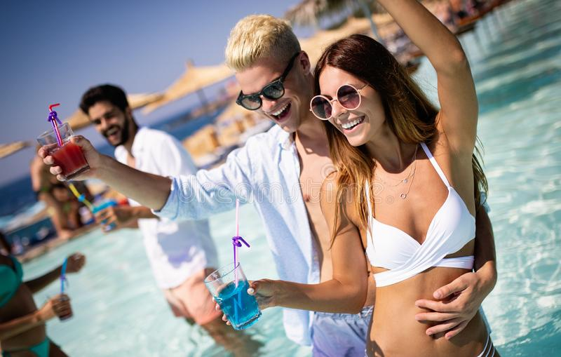 Group of happy friends having fun dancing at swimming pool outdoors. Group of happy friends having fun dancing at swimming pool with cocktails stock images