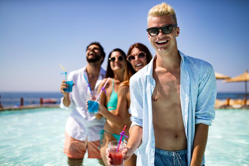 Group of happy friends having fun dancing at swimming pool outdoors. Group of happy friends having fun dancing at swimming pool with cocktails royalty free stock photos