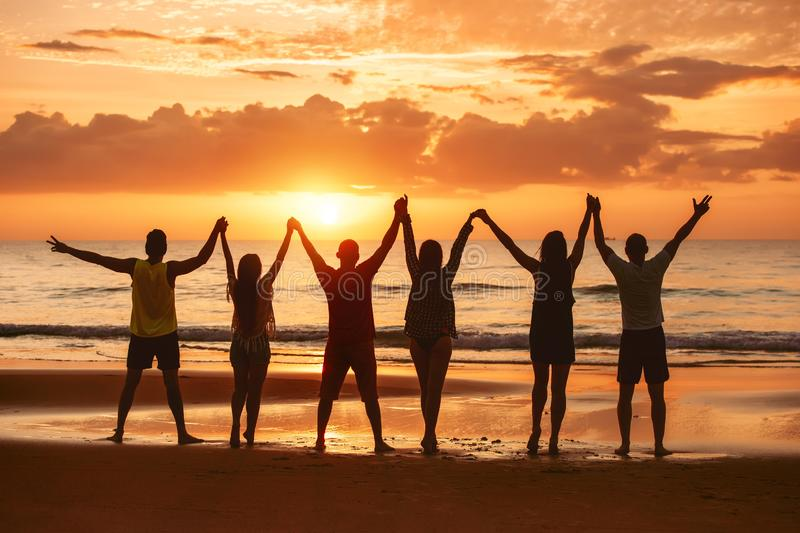 Happy friends raised arms together sunset sea royalty free stock photos