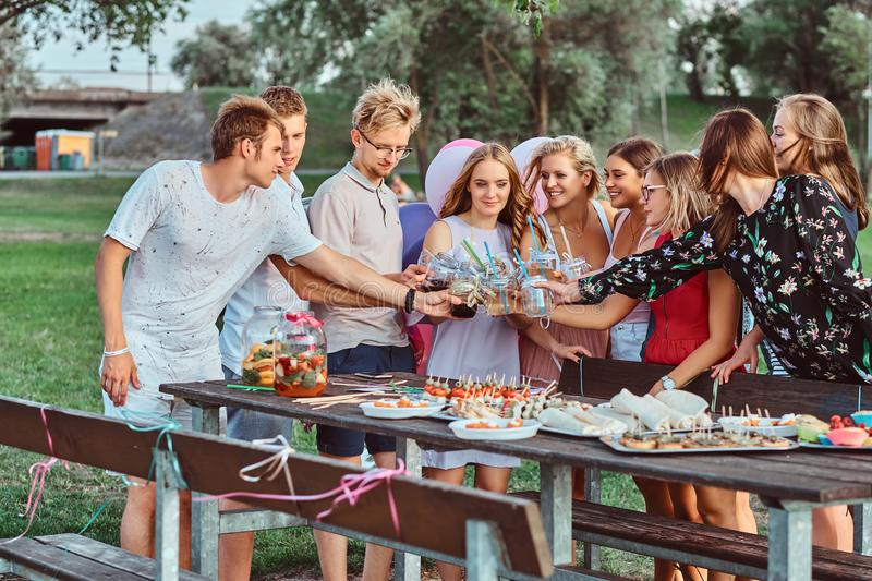 Group of happy friends having fun together celebrating a birthday at the outdoor park. Joyful friends cheering with royalty free stock photography