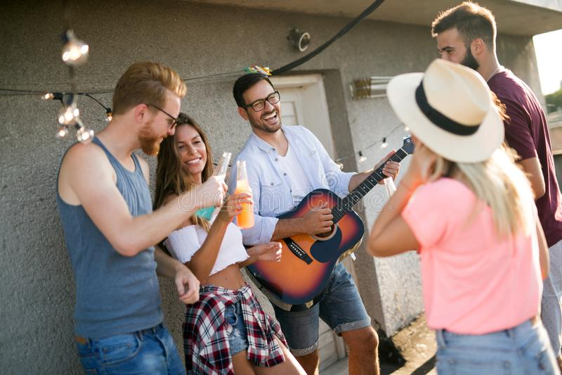 Group of happy friends having party on rooftop stock photography