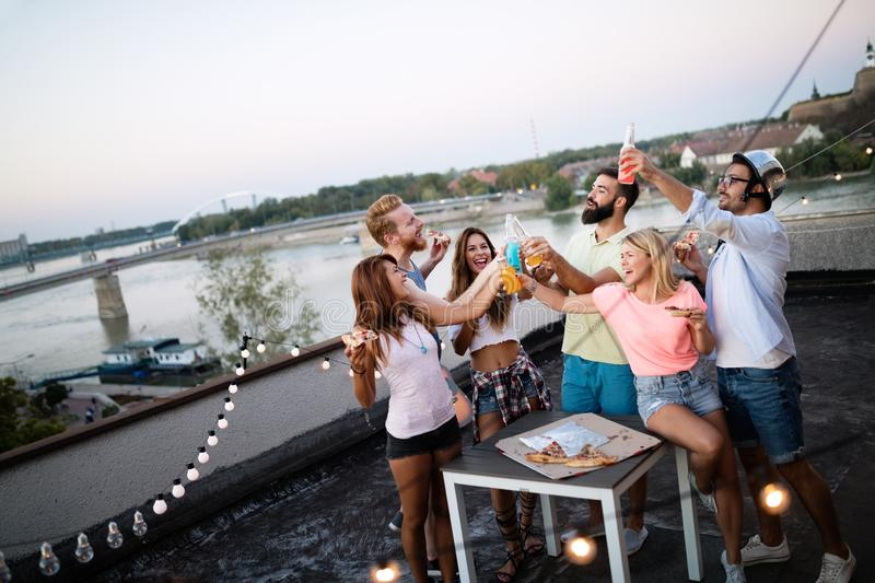 Group of happy friends having party on rooftop stock photo