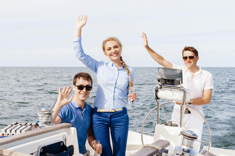 Group of happy friends having a party on a yacht and drinking ch royalty free stock images
