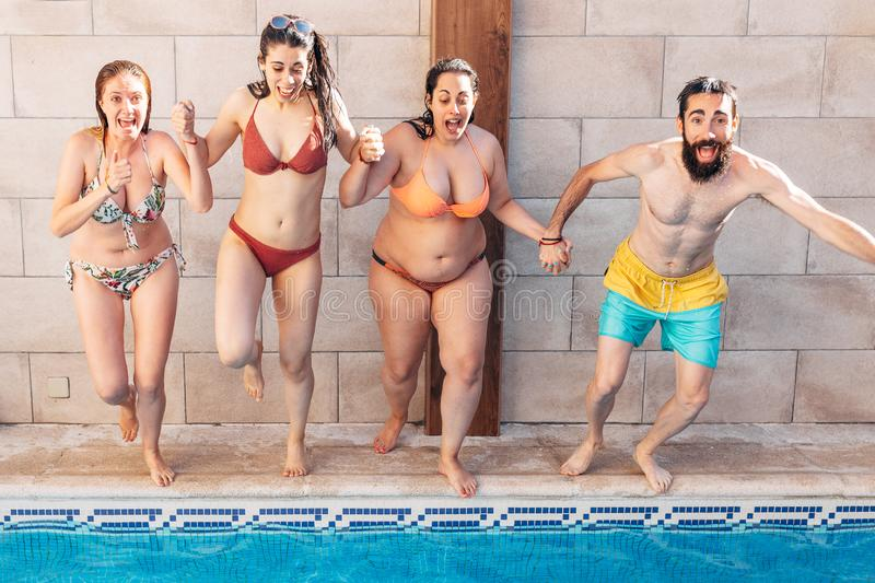 Group of happy friends holding hands and jumping in pool. Young diverse culture people having fun in vacation. Holiday and stock image