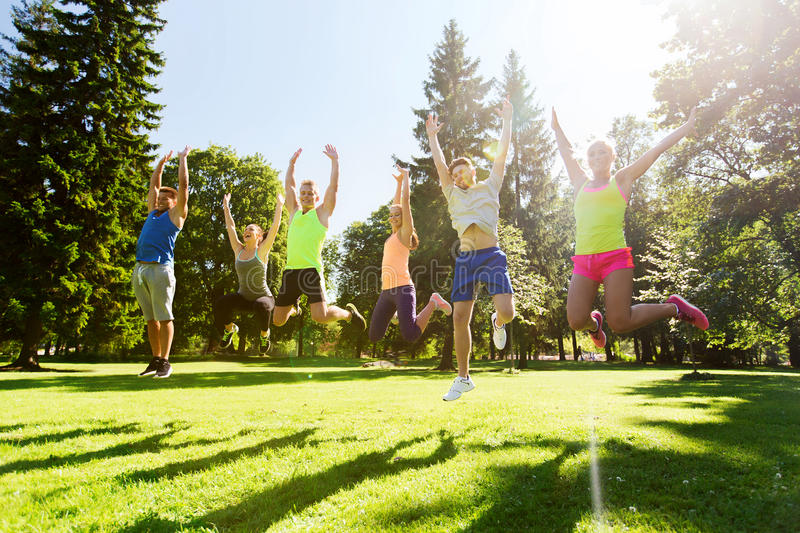 Group of happy friends jumping high outdoors stock images