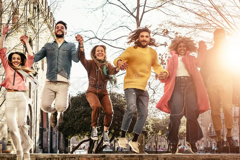 Group of happy friends jumping outdoor - Millennial young people having fun dancing and celebrating at sunset outside stock image