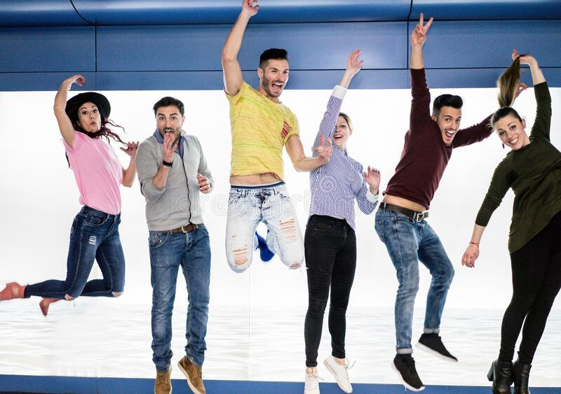 Group of happy friends jumping in underground metro station - Young people having fun together indoor - Happiness and freedom royalty free stock photo