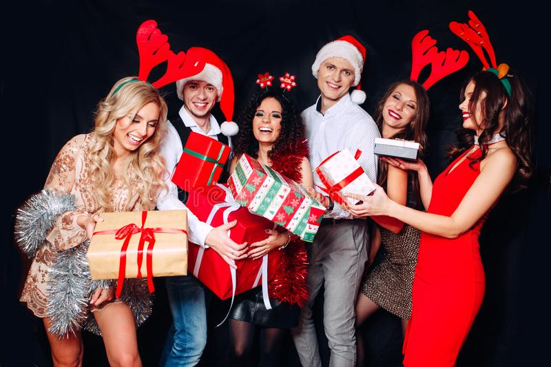 Group of funny friends laughing and sharing Christmas gifts. Friends celebrating Christmas or New Year eve party stock photography