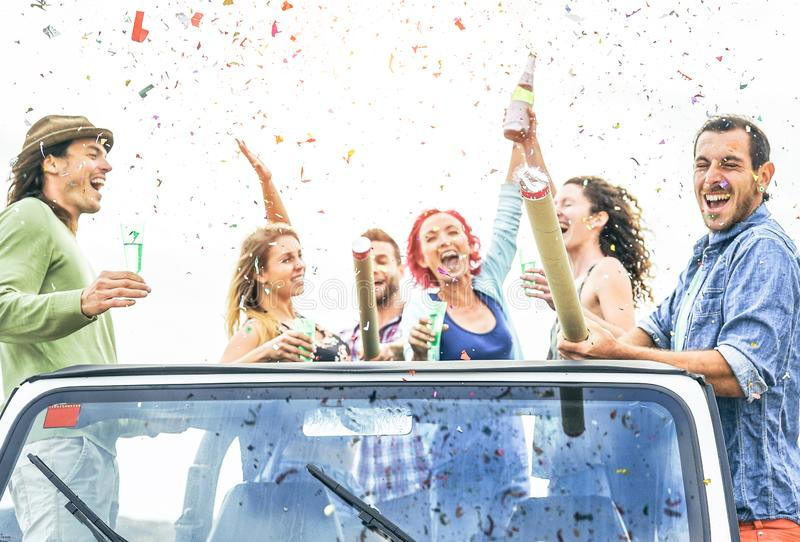Group of happy friends making party throwing confetti on convertible jeep car - Young people celebrating and having fun royalty free stock image