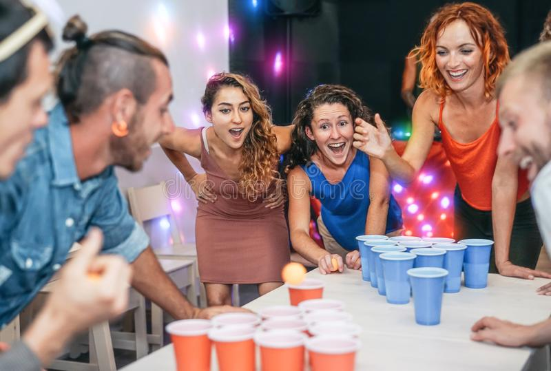 Group of happy friends playing beer pong in pub cocktail bar - Young millennials people having fun doing party alcohol games stock images