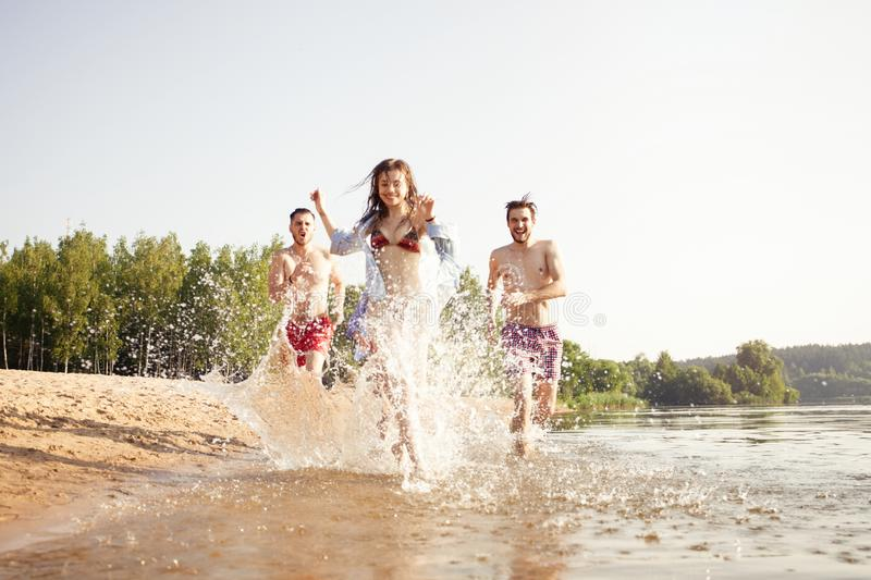 Group of happy friends running in to water - active people having fun on the beach on vacation. Tourists going to swim royalty free stock photo