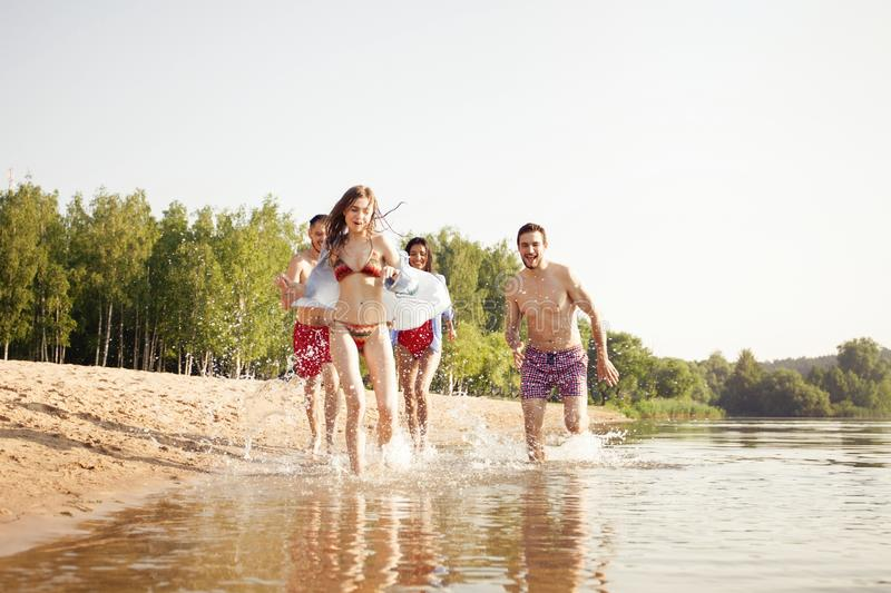 Group of happy friends running in to water - active people having fun on the beach on vacation. Tourists going to swim royalty free stock photos