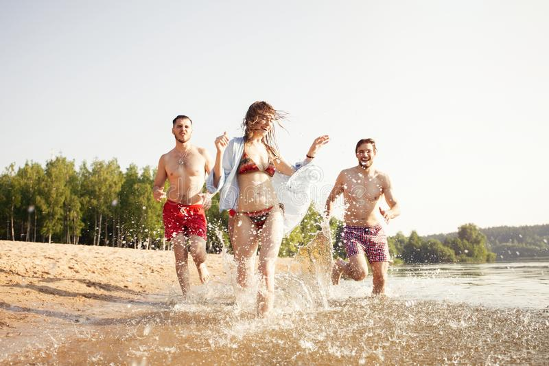 Group of happy friends running in to water - active people having fun on the beach on vacation. Tourists going to swim stock photo
