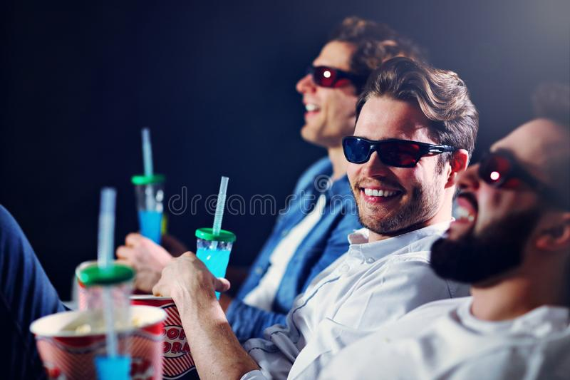 Group of happy friends sitting in cinema watch film and eating popcorn royalty free stock images