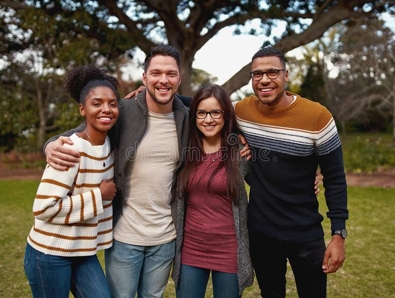 Portrait of a smiling diverse group of young friends standing together in the park outdoors on a sunny day stock photography