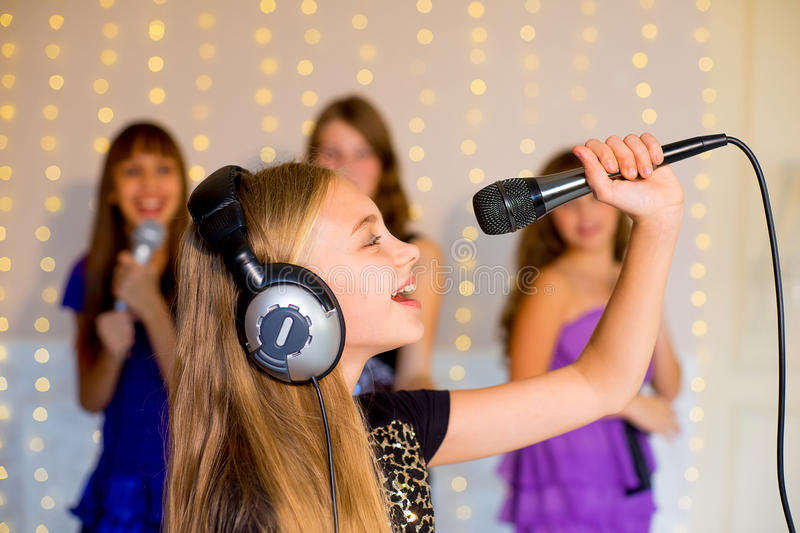 Group of happy girls singing on karaoke. Group of happy girls singing together on karaoke on background of lights with first plan of one girl royalty free stock photography