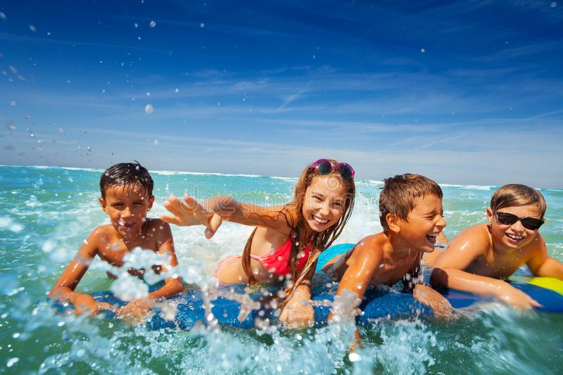 Group of happy kids boy and girls splash in sea royalty free stock images