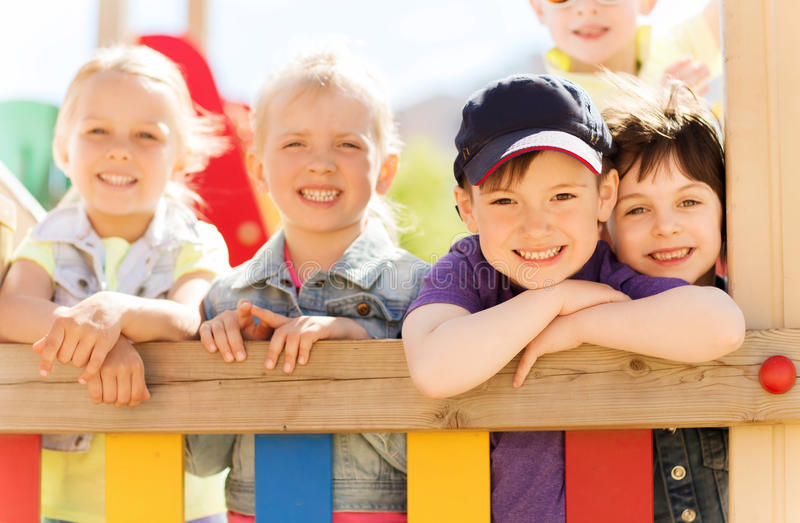 Group of happy kids on children playground. Summer, childhood, leisure, friendship and people concept - group of happy kids on children playground royalty free stock photography