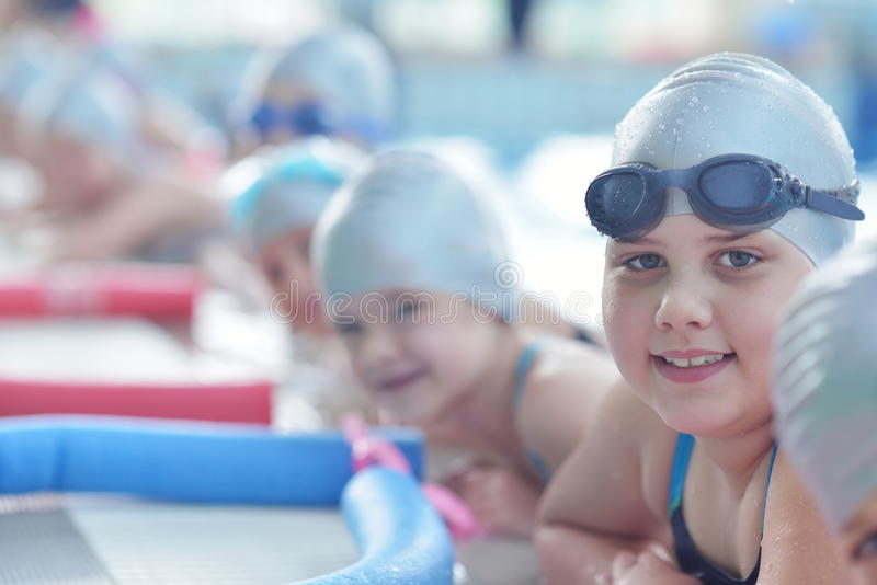 Group of happy kids children at swimming pool. Class learning to swim royalty free stock photo