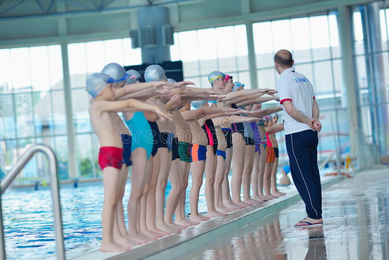 Group of happy kids children at swimming pool. Class learning to swim stock image
