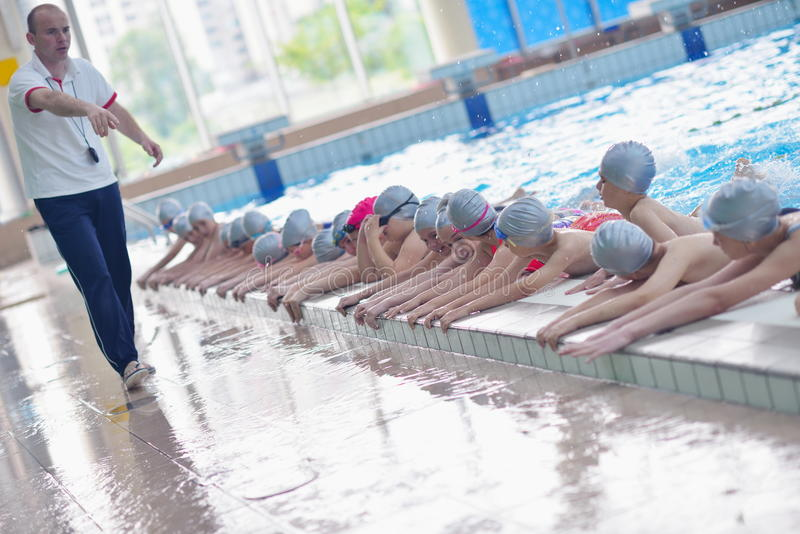 Group of happy kids children at swimming pool. Class learning to swim stock photos