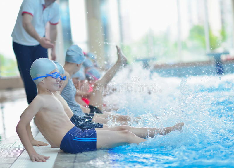 Group of happy kids children at swimming pool. Class learning to swim stock images