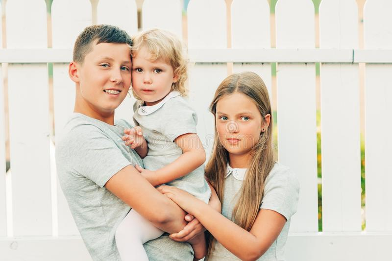 Group of 3 happy kids. Family with teenage boy, little girl and toddler, hugs and love royalty free stock photo