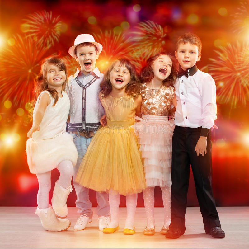 Group of happy kids in holiday clothes with fireworks background royalty free stock photos