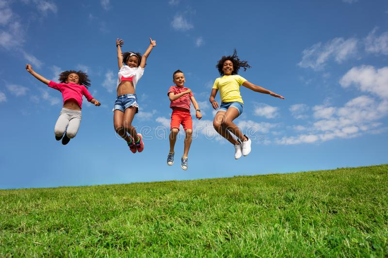 Group of happy kids jump high over sky on lawn royalty free stock photo