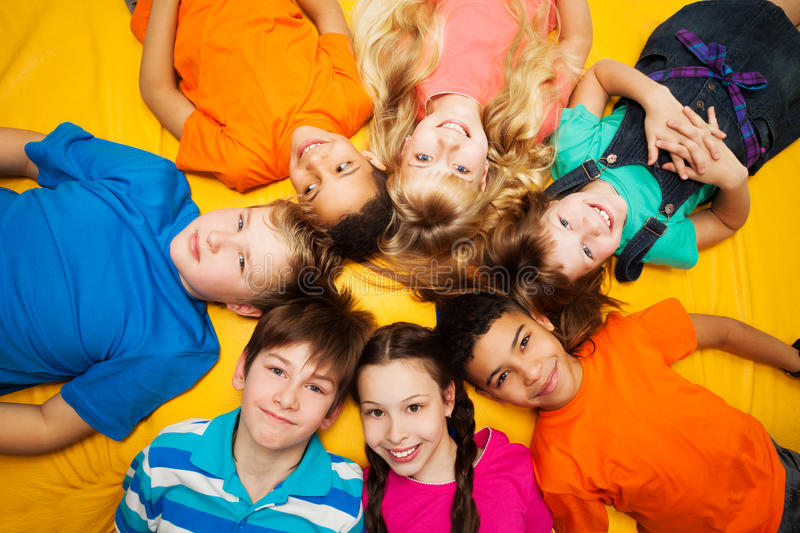 Group of happy kids laying in circle royalty free stock images