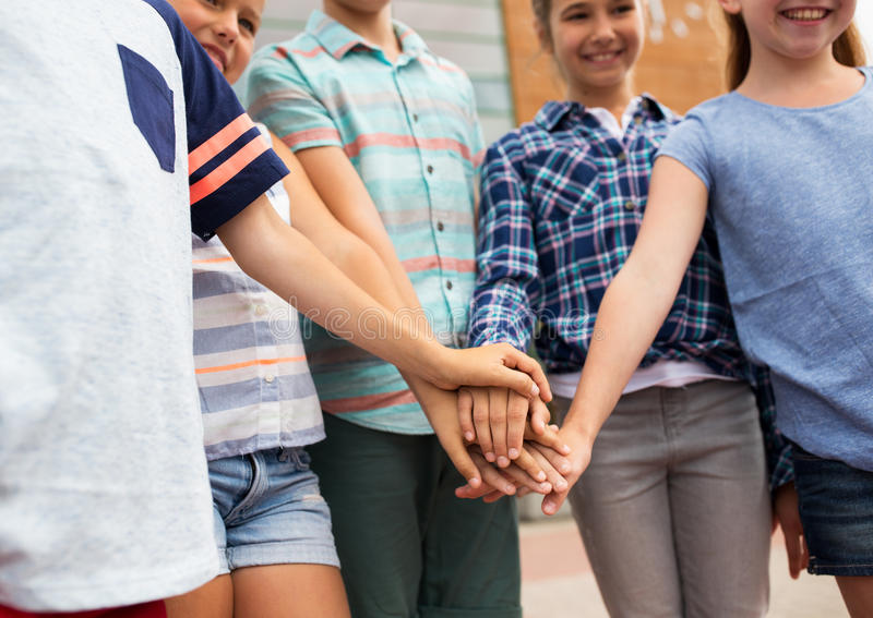 Group of happy kids putting hands together. Summer holidays, friendship, childhood, leisure and people concept - group of happy pre-teen kids putting hands stock photography