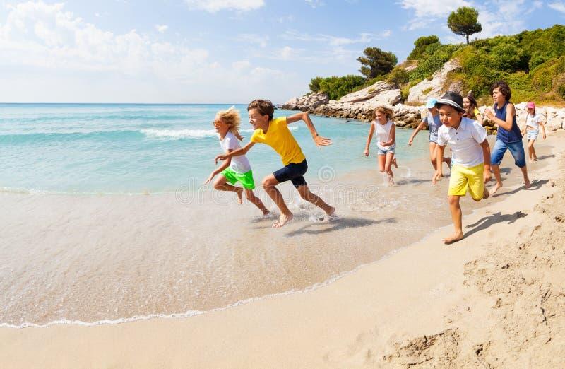 Group of happy kids racing on sandy beach stock photography