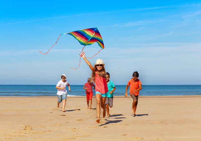 Group of happy kids run with kite on the beach royalty free stock image