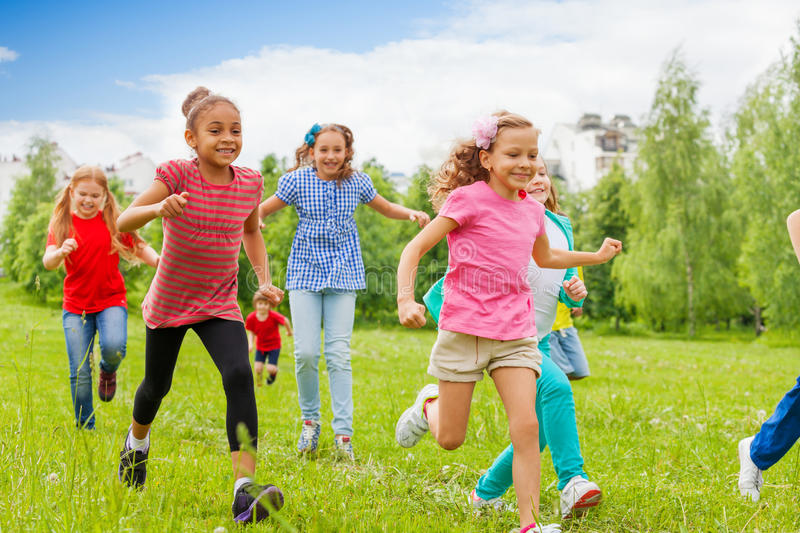 Group of happy kids running through green field stock images