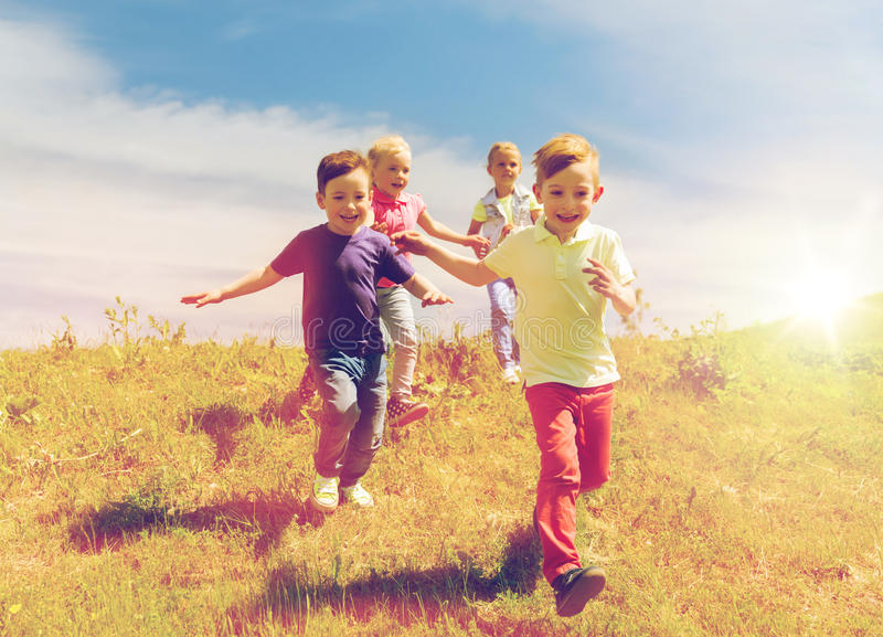 Group of happy kids running outdoors royalty free stock images