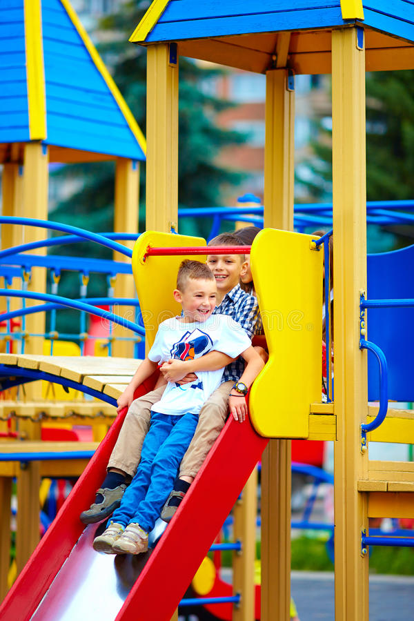 Group of happy kids sliding in colorful playground royalty free stock photography