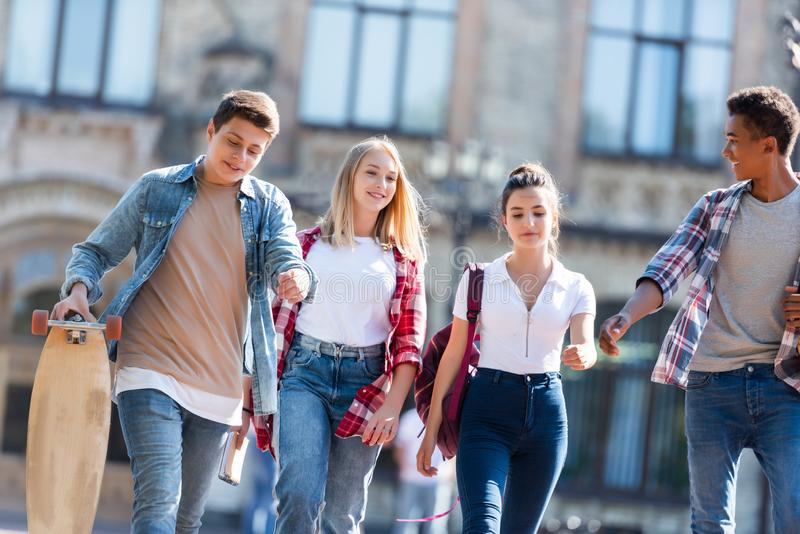 Group of happy multiethnic teenagers with backpacks having walk together with old school building. On background stock photography
