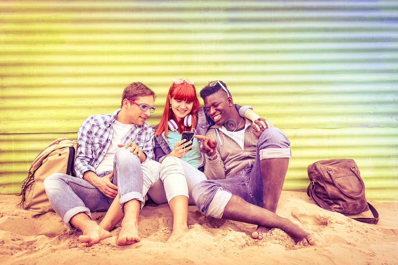 Group of happy multiracial friends having fun together with phone stock images