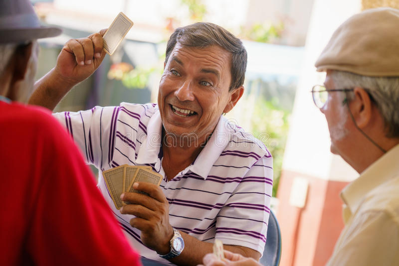 Group Of Happy Old Friends Playing Cards And Laughing. Happy active retired people, old hispanic friends having fun, seniors playing cards at home royalty free stock photos