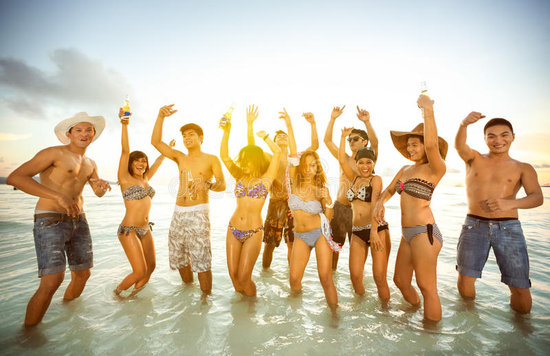 Group of happy people dancing at the beach stock image