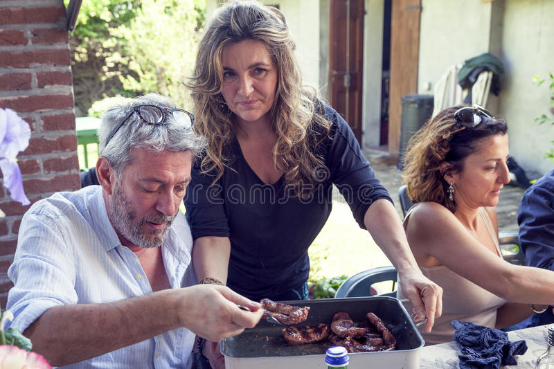 Group of happy people is eating meat outdoors. Group of happy people is eating meat in a farm outdoors royalty free stock photography