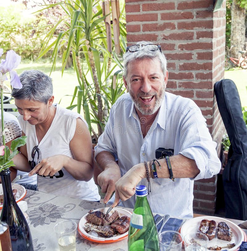 Group of happy people is eating meat outdoors. Group of happy people is eating meat in a farm outdoors stock photos