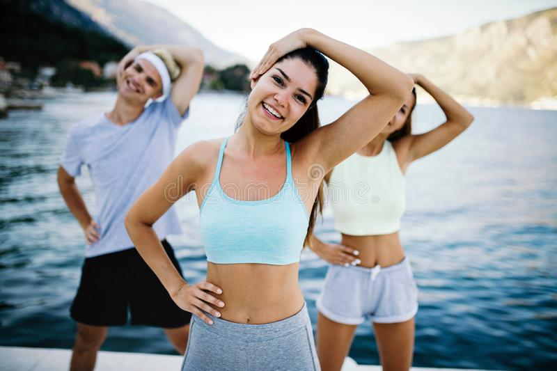 Group of happy people exercising outdoor. Sport, fitness, friendship and healthy lifestyle concept royalty free stock images