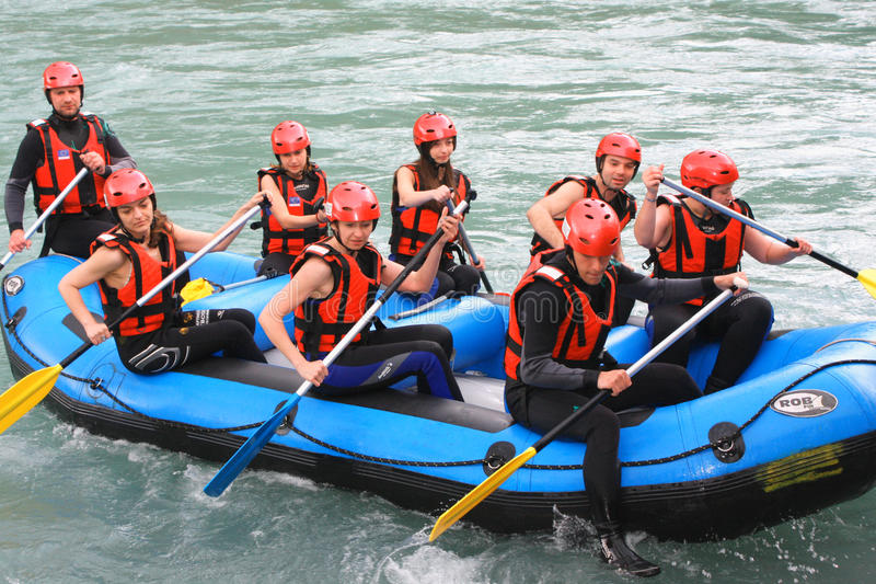 Group of happy people with guide whitewater rafting and rowing o stock photography